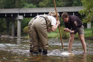 national_park_service_volunteer_helps_students_check_a_rock_for_insects_9895390493